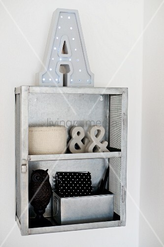Ornaments in shades of grey and black in small, open-fronted shelf unit