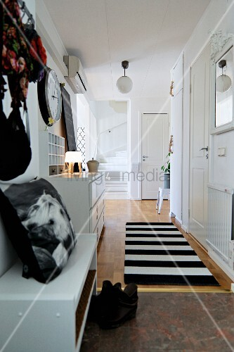 White hallway with black accessories, runner with wide stripes and foot of staircase at far end