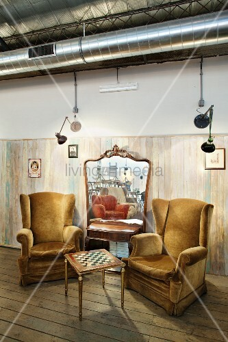 Comfortable seating area with chessboard table and plush reading chairs in front of large mirror leaning on wall