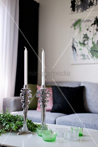 White candles in silver candlesticks and tealight holders on coffee table in front of pale grey sofa