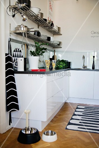 Detail of kitchen counter with white base units and animal feeding bowls on parquet floor