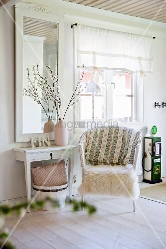 rattansessel mit weissem fell und wandtisch vor gerahmtem spiegel an wand in l ndlichem wohnraum. Black Bedroom Furniture Sets. Home Design Ideas