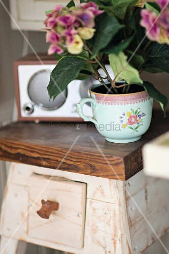 Hydrangea planted in vintage teacup on rustic wooden flower stand