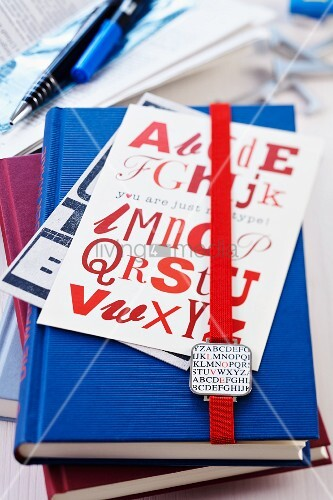 Bookmark and postcards with alphabet pattern on stack of books