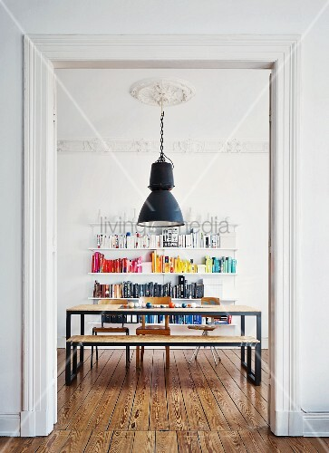 DIY, chipboard dining set with black frames below vintage industrial lamp hanging from stucco ceiling in front of colourful books on shelving