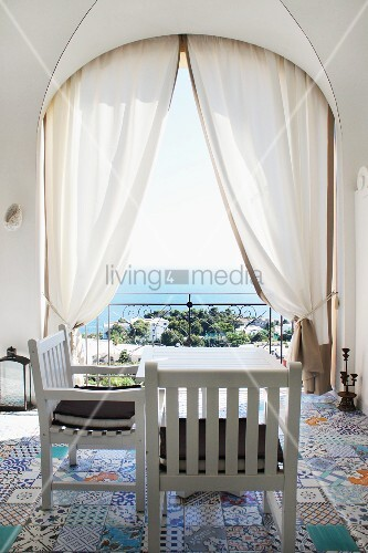 White wooden chairs and table on colourful, patterned, old floor tiles in loggia with view over Capri bay