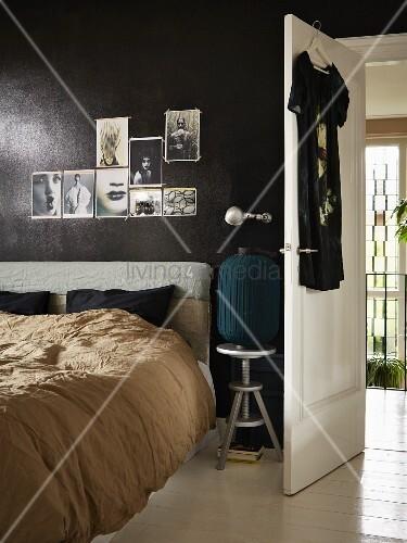 Bett mit kopfpolster vor schwarz get nter wand mit angehefteten fotos daneben die offene - Fotos an die wand ...