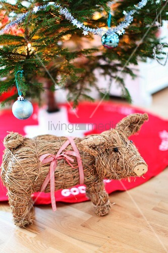 Straw pig in front of partially visible Christmas tree