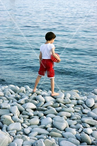 Little boy in red shorts holding ball on pebbly beach
