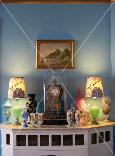 Various Painted Vases And Table Clock Under Glass Cover On Wood Clad