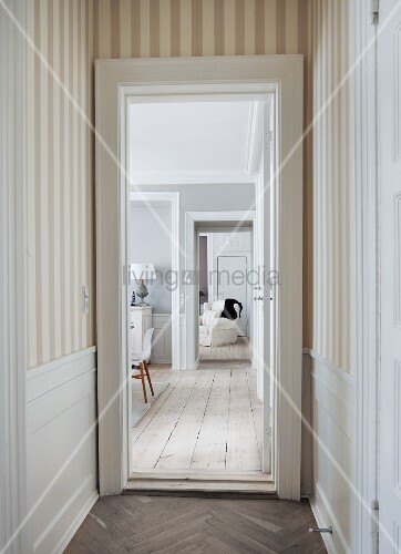 View From Narrow Hallway With Striped Wallpaper And Herringbone Parquet Into Living Area Rustic Wooden Floor