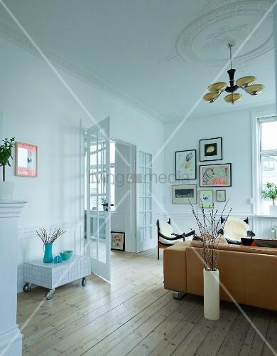 Wohnzimmer Mit Rustikalem Flair, Art Deco Hängeleuchte An Stuckdecke, über  Sofa Und Sesseln, Seitlich Offene Flügeltür
