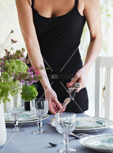 Young woman setting table