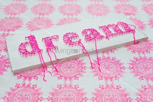 White-painted board with motto written in pink using threads wrapped around pins on fabric background with ornamental pattern