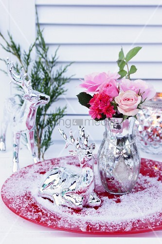 Bouquet of roses in mercury glass vase and deer ornament in artificial snow on red plate