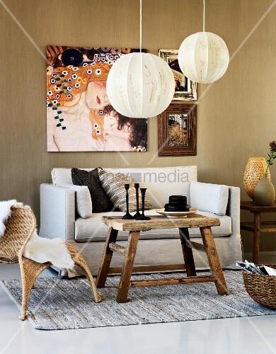 schlichte ballonleuchten ber rustikalem tisch geflechtstuhl und sofa an wand unter gem lde von. Black Bedroom Furniture Sets. Home Design Ideas