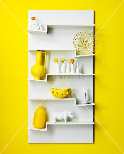 White wall-mounted shelving unit with ornaments on zigzag shelves on yellow wall