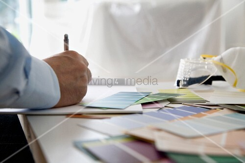 A man sitting at a table with colour samples