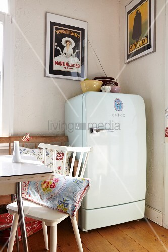 White fifties fridge in dining room with vintage advertising posters ...