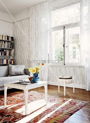 weisser beistelltisch mit blumenstrauss auf teppich vor fenster mit bodenlangem transparentem. Black Bedroom Furniture Sets. Home Design Ideas