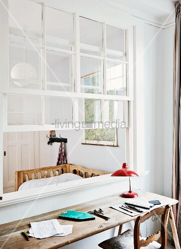 Rustic desk with wooden top and retro, red table lamp in front of interior, lattice sash window