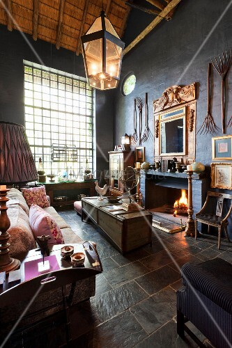 Lounge area with pale sofa and antique collectors' items in high-ceilinged interior with open fireplace and lattice windows