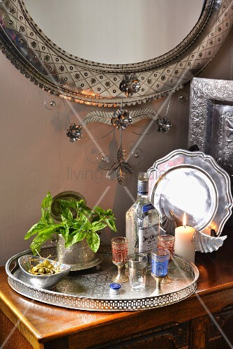 Glasses, bottle, dish of capers and potted herbs on Oriental silver tray
