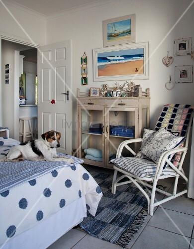 hund auf bett gegen ber weisser bambusstuhl mit kissen neben kommode mit glast ren in l ndlich. Black Bedroom Furniture Sets. Home Design Ideas