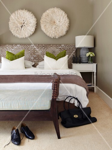 Fluffy, round wall decorations on grey-painted wall above double bed with bedroom bench at foot