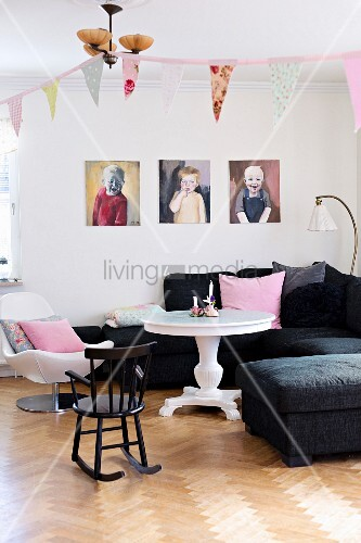 Lounge area with portrait paintings of children above black sofa, white round table and child's rocking chair on well-kept oak floor