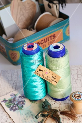 Reels of thread and tape measure in front of vintage biscuit tin