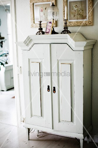 White-painted cabinet with feet below framed pictures on wall
