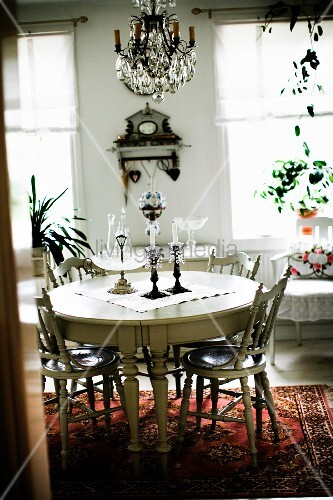 Round dining table and chairs with turned legs painted white in rustic interior