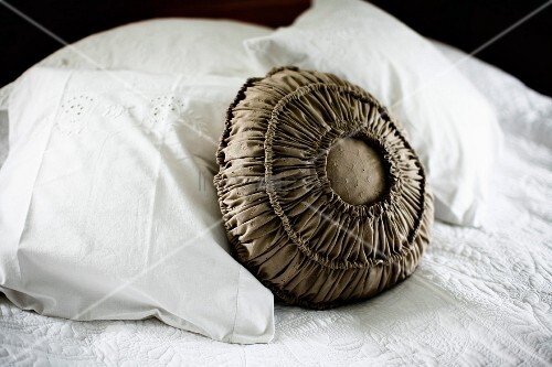 Cushion with ruched, brown-grey fabric cover amongst white pillows