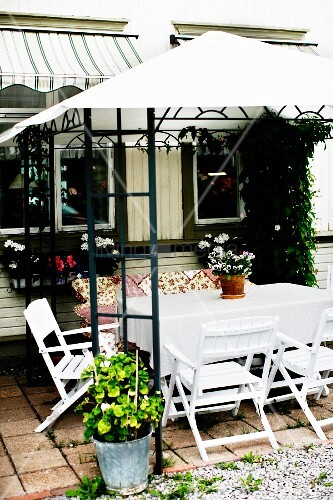 Seating area on terrace adjoining house; white-painted wooden chairs around table below pergola with white, fabric tent roof