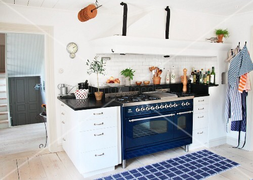 Blue rug in front of kitchen counter with blue, retro cooker and integrated extractor hood