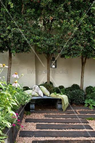 Courtyard with dark wooden sleepers set in gravel floor