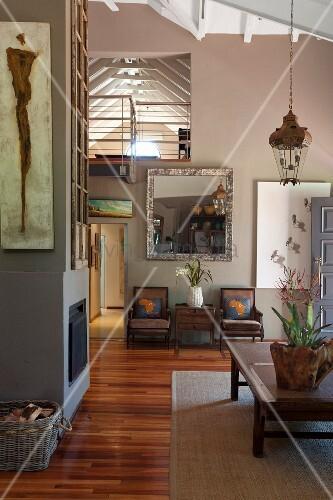 Offener Wohnraum mit Kaminwand und Blick auf Galerie unter sichtbarer Dachkonstruktion