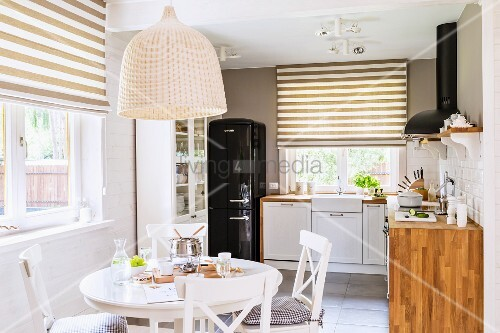 Table next to window with half-closed, white and brown striped roller blinds in kitchen-dining room
