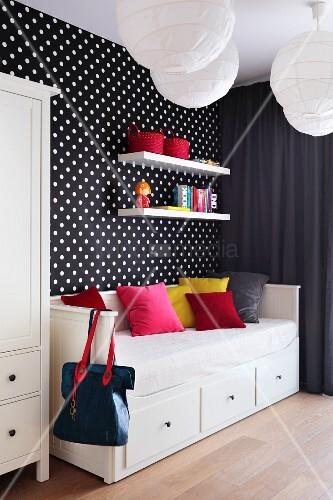 Farbige Kissen auf Schlafsofa mit Schubladen vor schwarzweiss gepunkteter Tapetenwand