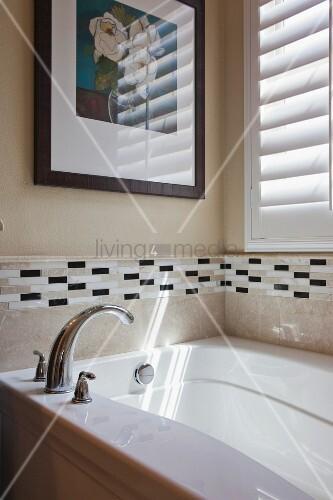 badewanne mit armatur vor gefliester wand dar ber gerahmtes bild neben fenster mit. Black Bedroom Furniture Sets. Home Design Ideas