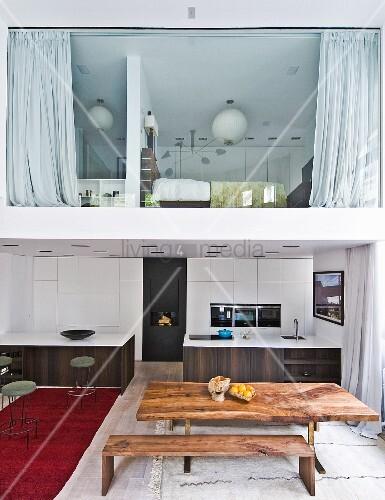 holztisch mit passender bank vor offener k che mit zwei monolithischen theken unter galerie mit. Black Bedroom Furniture Sets. Home Design Ideas