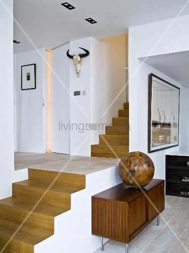 Wooden sphere on fifties-style sideboard against open staircase, view into hallway and hunting trophy on wall