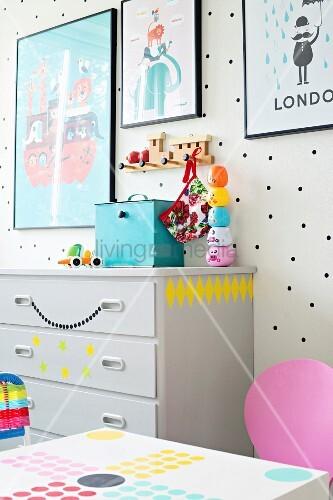 Gerahmte Plakate an weißer Wand mit schwarzen Punkten und Kinderspielzeug auf grauer Kommode mit Deko-Aufklebern