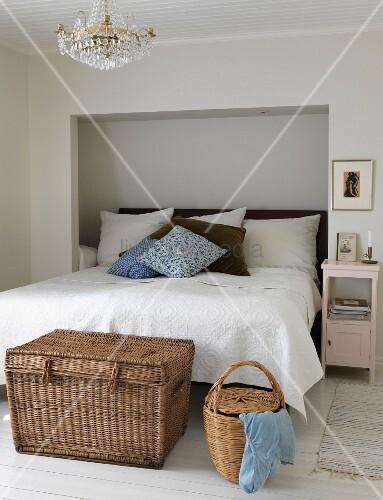 Wäschetruhe aus Rattan vor Doppelbett, teilweise in Nische in ...