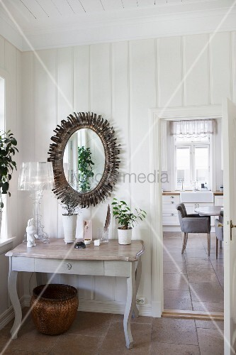 Console table with curved legs below mirror with sunburst frame on wooden wall