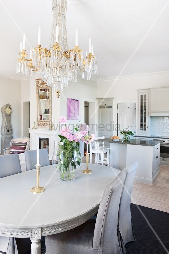 Chairs With Grey Loose Covers Around Neo Classical Dining Table Below Chandelier In Open