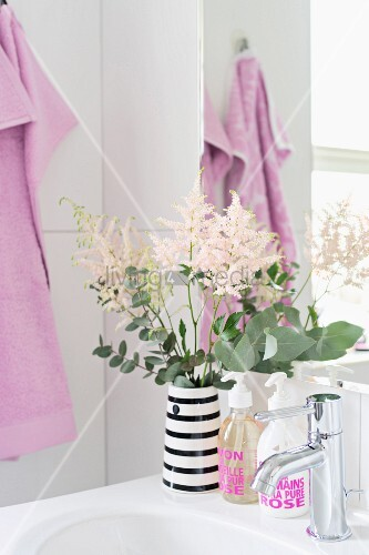 Vase of flowers on sink and soap dispensers with pink lettering