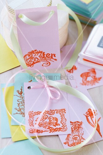 Bunte Geschenkanhänger aus Papier bestempelt mit Oster- und Frühlingsmotiven.