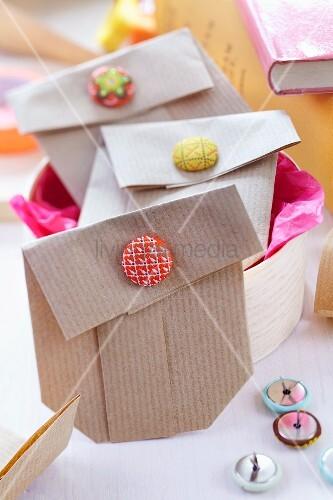 Kleine Geschenktütchen gefaltet aus Packpapier verschlossen mit Knopfklammern